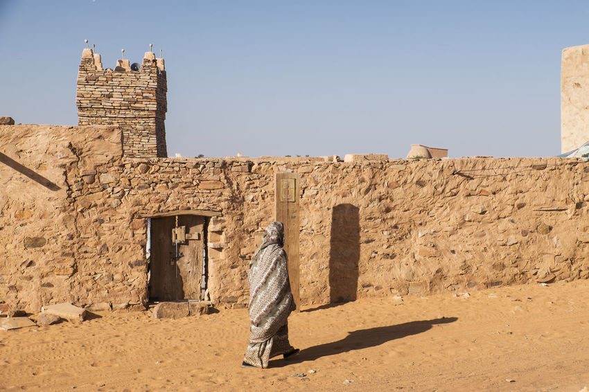 Street view whit traditional weared person in famous town of Chinguetti Africa Traditional Culture CHINGUETTI Tourism Destination Travel Destinations Attraction Heritage Building Traditional Clothes Muslim Islam Desert Mauritania Rock Traditional Craft