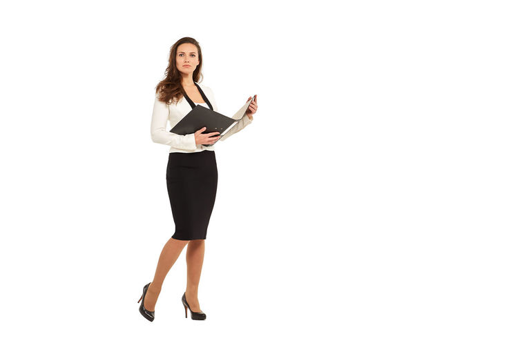 Full length portrait of young woman standing against white background