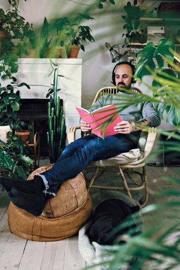 Portrait of man sitting on potted plant
