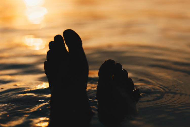 Body Part Close-up Feet Finger Hand Human Body Part Human Foot Human Hand Human Leg Human Limb Land Leisure Activity Lifestyles Nature One Person Outdoors Real People Sea Selective Focus Sunlight Sunset Water
