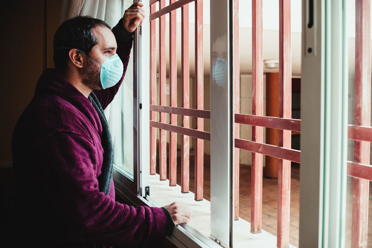 Man standing by window at home