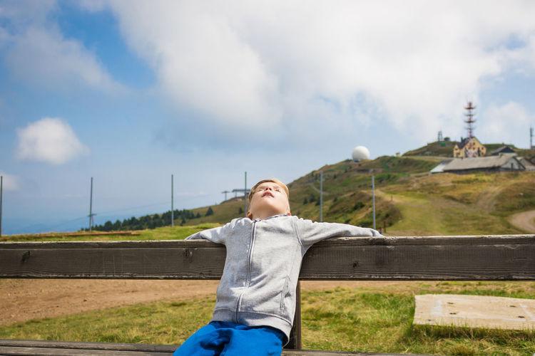 Boy sitting on bench against sky