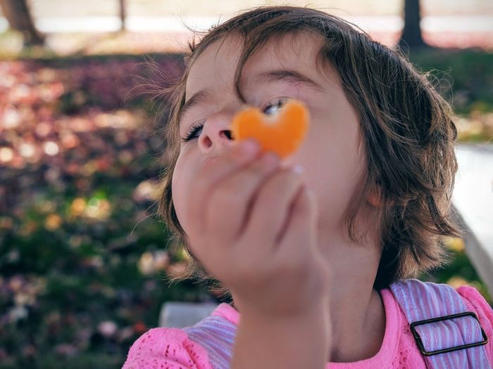Close-up of girl showing orange heart shape candy