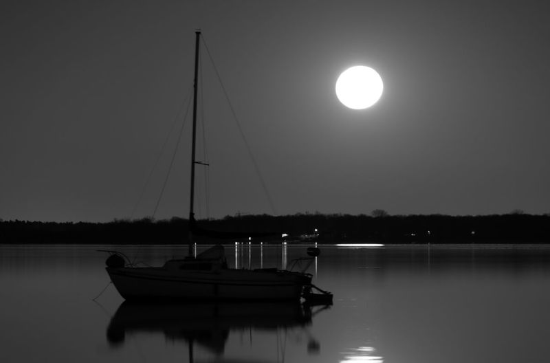 Sailboat under a full moon anchored in a mirror like lake Water Nautical Vessel Transportation Lake Reflection Tranquility Tranquil Scene Mode Of Transportation Sky Waterfront Scenics - Nature Beauty In Nature Nature No People Sailboat Night Moon Moored Outdoors Full Moon Moonlight