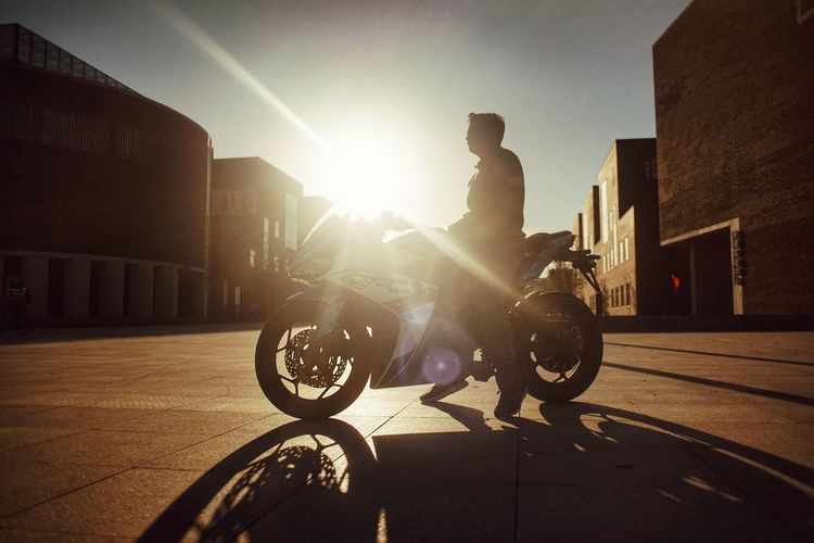 Silhouette Architecture Bright Building Exterior Built Structure City Full Length Land Vehicle Lens Flare Mode Of Transportation Nature One Person Real People Ride Riding Shadow Sky Street Sun Sunbeam Sunlight Transportation