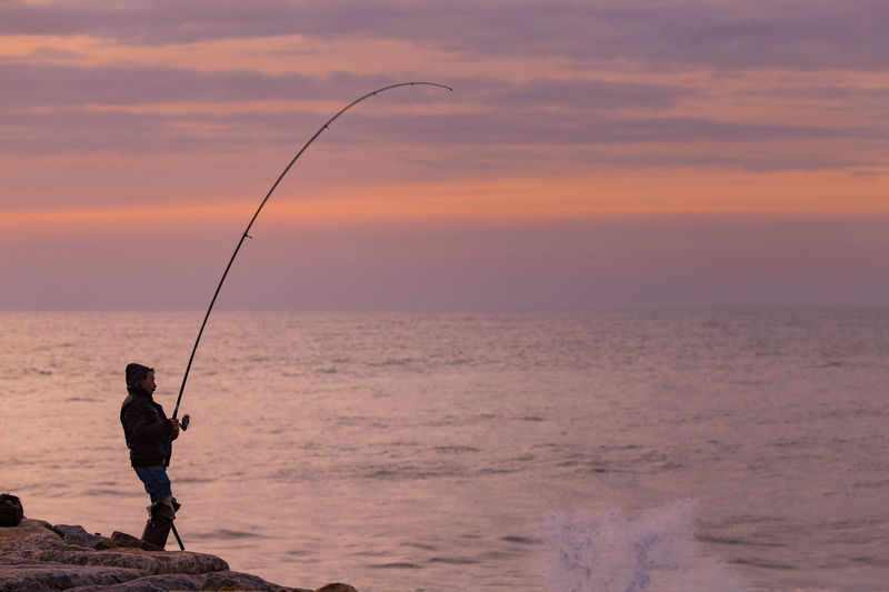 Fishing at Furadouro Beach, Portugal Atlantic Ocean Beach Breakwater Catch Fish Fisherman Fishing Fishing Rod Fishing Time Furadouro Golden Hour Hobby Idyllic Nature Orange Color Outdoors Ovar Portugal Scenics Seafood Silhouette Sunset Sunset Silhouettes Sunset_collection Waves