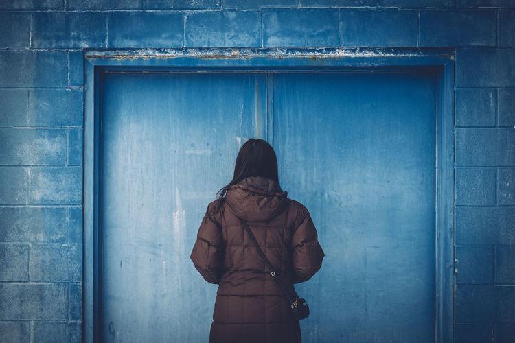 Rear view of woman standing in front of closed wooden door