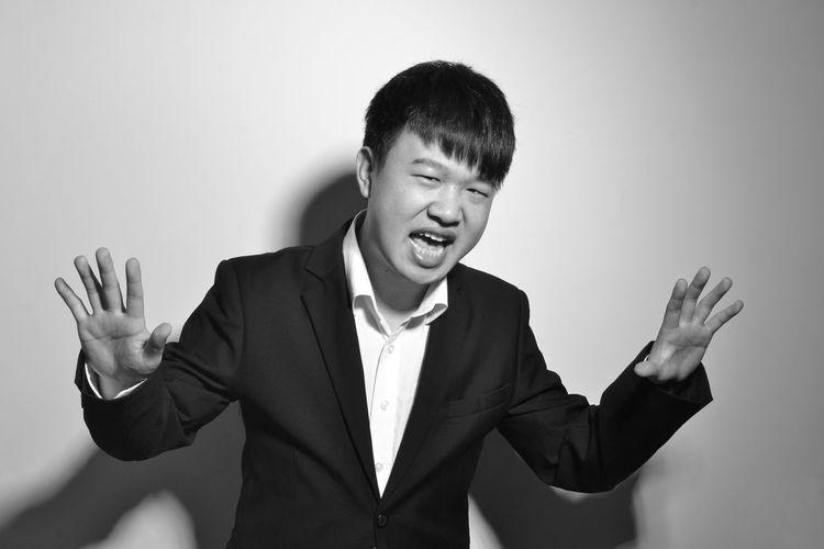Portrait of young man gesturing against gray background