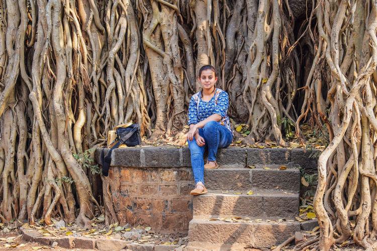 Full length portrait of woman sitting against tree