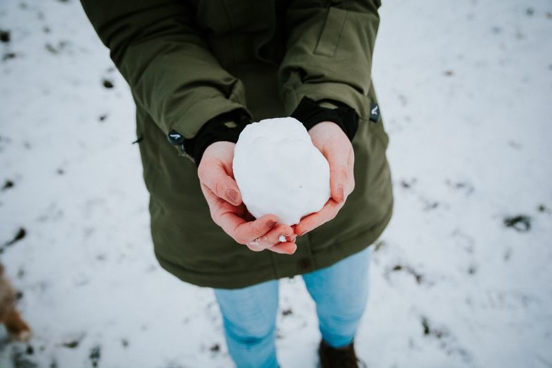 Close-Up Of Hands Holding A Snowball