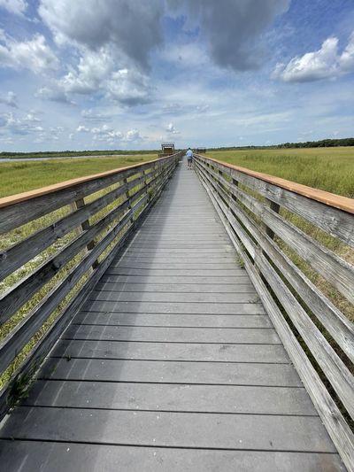 Empty boardwalk leading towards landscape against sky