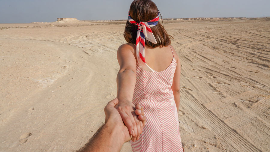 Rear view of woman on beach, holding hands