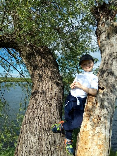 One Person Tree Day Tree Trunk Childhood Full Length Casual Clothing Outdoors Standing Girls Leisure Activity Real People Smiling Nature Lifestyles Portrait Child Children Only People Sky