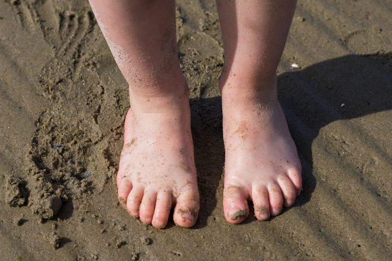 Low section of child standing at beach