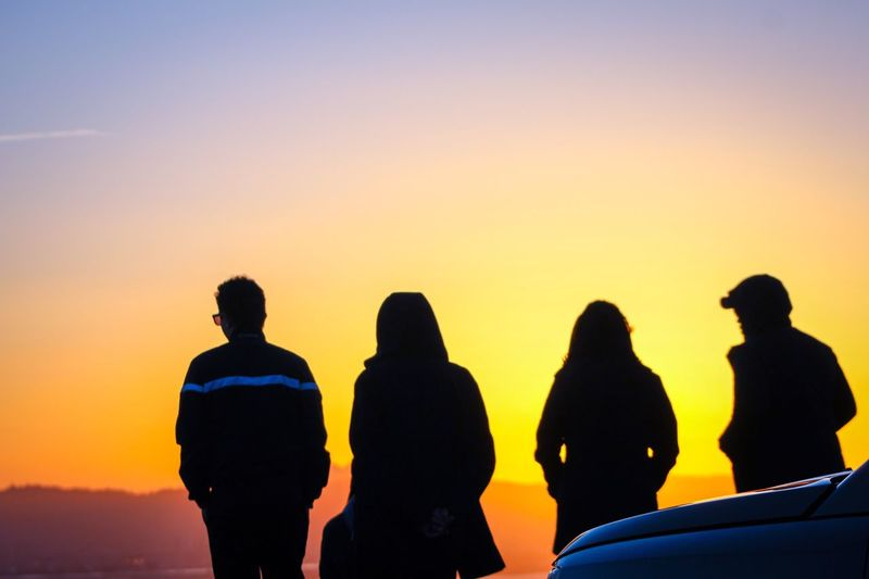 Rear view of friends standing against sky during sunset