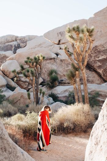 Woman standing by rocky mountains at joshua tree national park