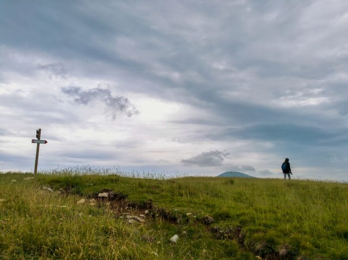 Cloud - Sky Grass Cloudscape Dramatic Sky Landscape Outdoors Nature Field Beauty In Nature Travel Destinations Scenics Storm Cloud One Person Day Adult People Sky Enjoying Life Tranquility Lifestyles Hiking, Mountains, Adventure Sign Post Loneliness Walking Low Section Lost In The Landscape
