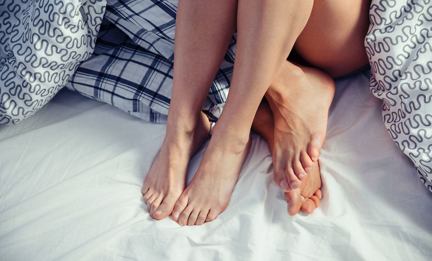 Low Section Of Couple Sitting On Bed