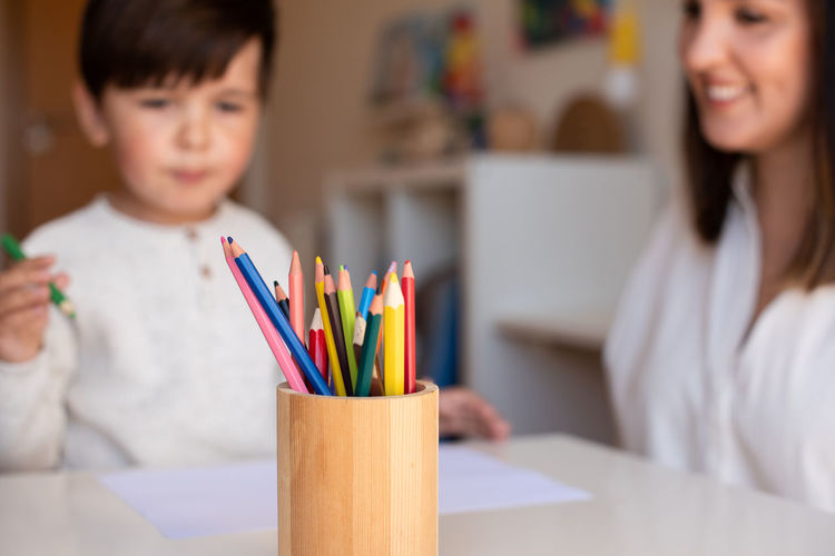 Portrait of boy holding colored pencils on table