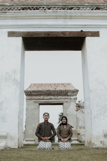 Portrait of couple wearing traditional clothing kneeling at temple