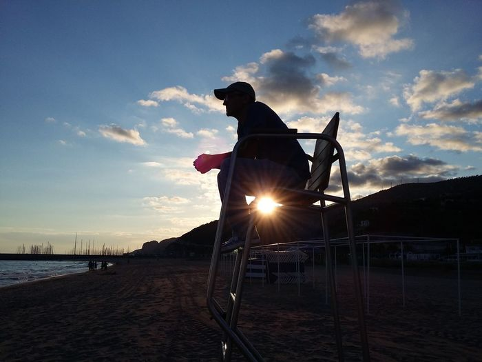 Man sitting on lifeguard chair at beach against sky during sunset