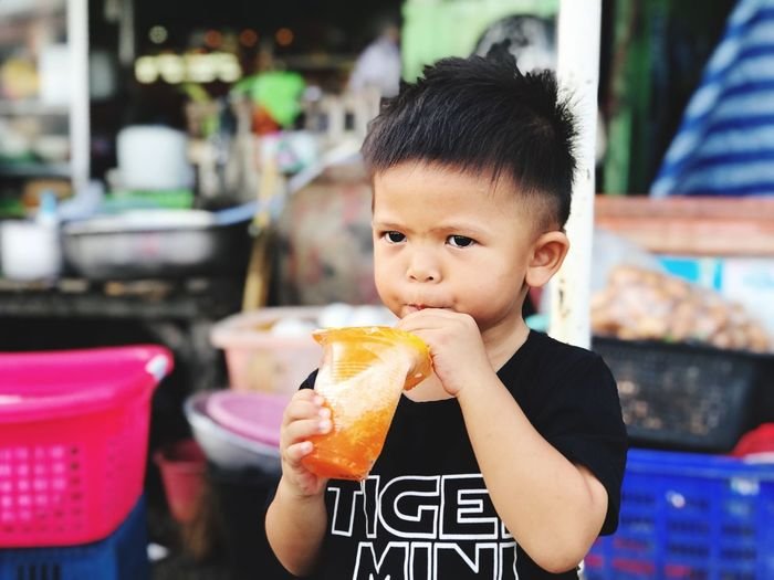 Close-up of boy having drink while standing outdoors