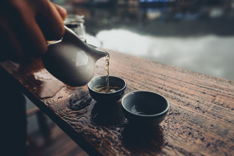 Cropped hand holding tea pot over cup on table