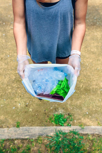 Low Section Of Woman Holding Garbage In Plastic Bag On Footpath