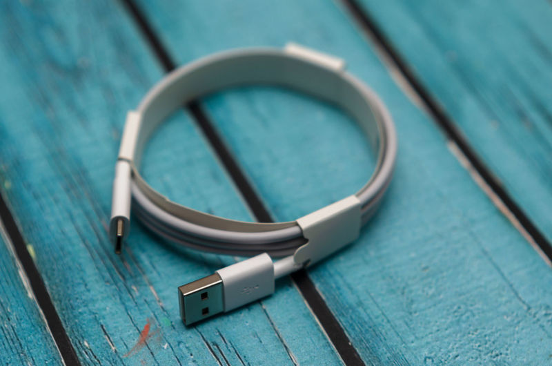 Usb type cable with white color on a blue wooden background in blur.