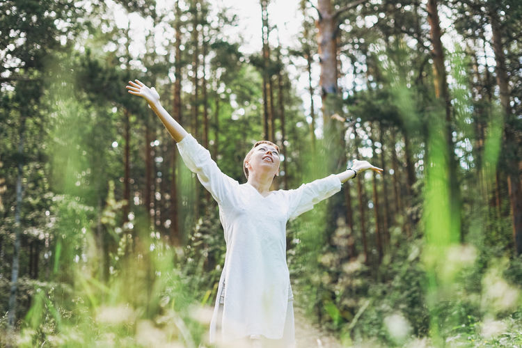 Woman with arms raised standing in forest