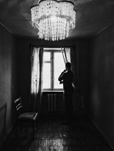 Side view of man standing by window at home