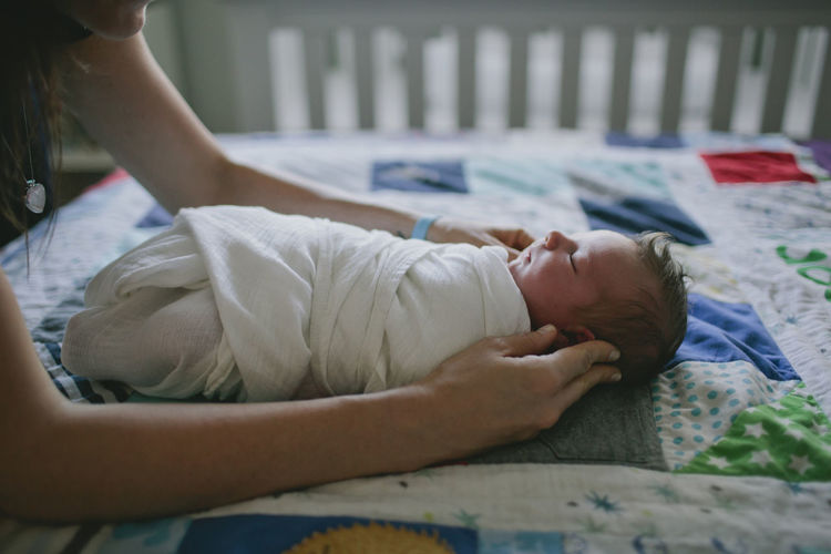 Cropped image of mother touching wrapped baby on bed at home