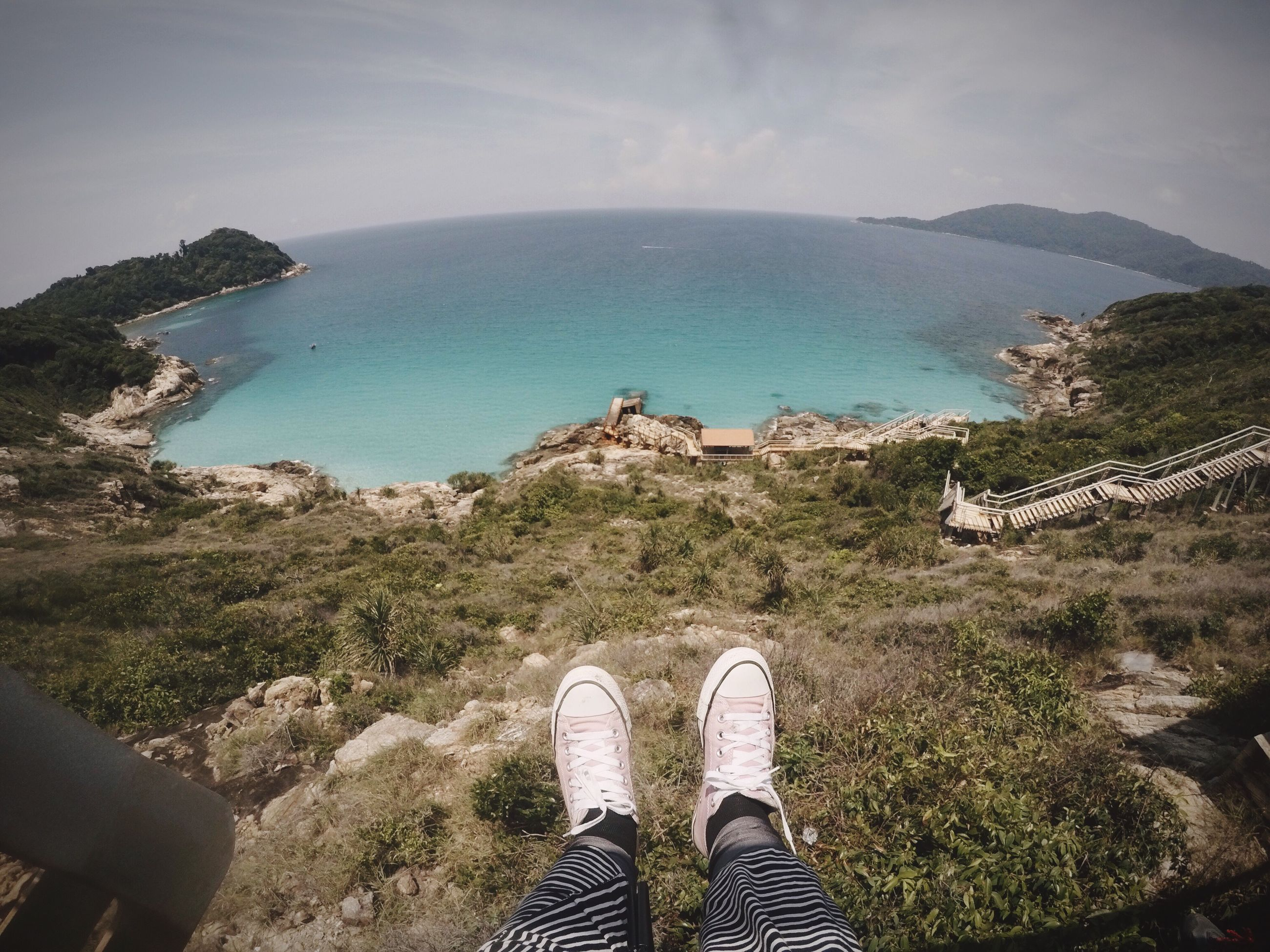 high angle view, personal perspective, water, scenics, nature, beauty in nature, day, real people, mountain, one person, sea, shoe, human leg, tranquility, cliff, sky, low section, outdoors, plant, landscape, standing, horizon over water, people