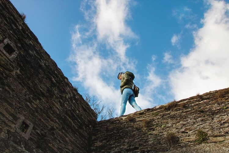 Low angle view of woman walking on surrounding wall against cloudy sky