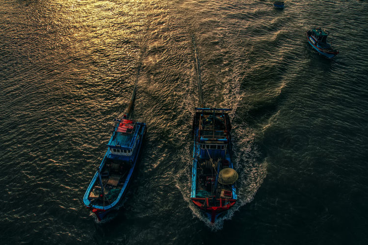 High angle view of boats sailing in sea during sunset