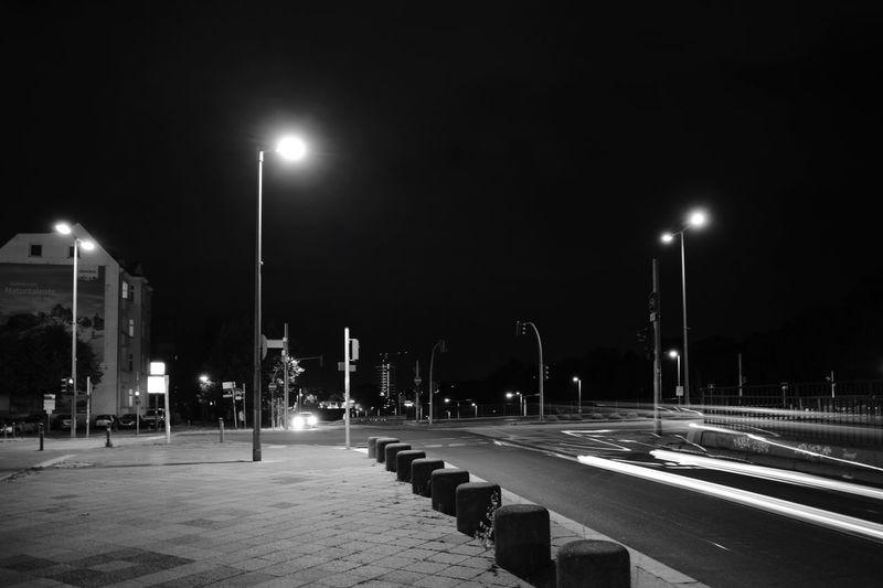 Empty road against illuminated street lights in city at night