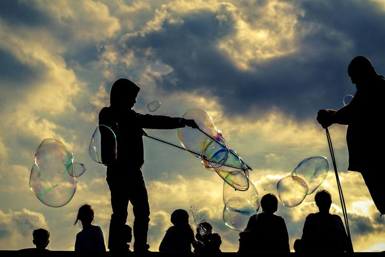 Silhouette people with bubbles against sky