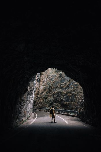 Side View Of Man Standing On Road Seen Through Tunnel