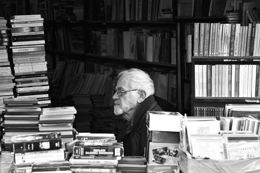 """""""Lost in Books"""" Blackandwhite Photography EyeEm Gallery Eye4photography  Reading A Book Book Old But Awesome One Person Headwear One Man Only Bookstore Occupation Retail  The Week on EyeEm Athens, Greece Stack Book Senior Adult One Senior Man Only Bookshelf Only Men One Man Only Abundance Large Group Of Objects Adult Business Finance And Industry Library People Business Old-fashioned Wisdom"""