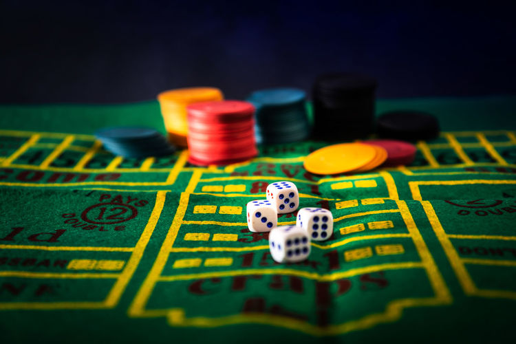 Close-Up Of Gambling Chips And Dices On Table At Casino