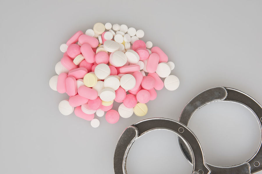 Silver handcuffs and stack of tablets place on white background. Care Copy Space Crime Doctor  Drug Medicine Overdose Pharmacy Pink Tablet Therapy Cuffs Handcuffs  Health Healthy Illegal Law Medical Pill Police Still Life Studio Shot Treatment White Yellow