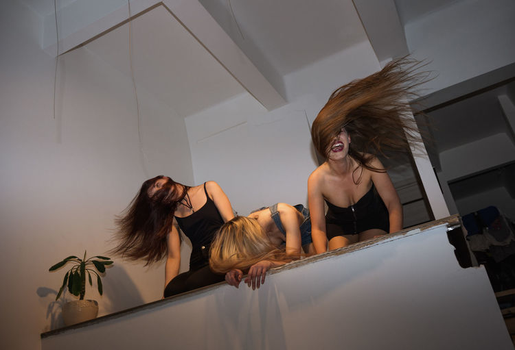 Low angle view of women tossing hair at home
