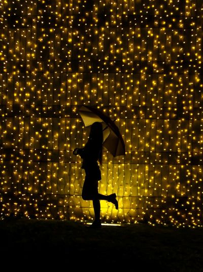 Silhouette woman with umbrella standing against illuminated string lights at night