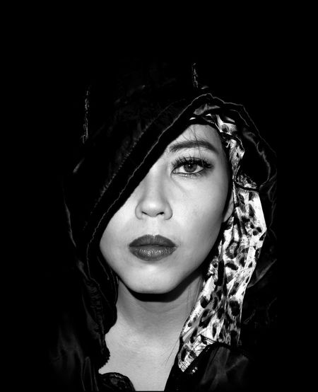 Close-up portrait of woman wearing hood against black background