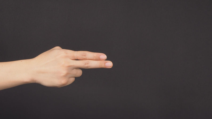 Close-up of hand gesturing against gray background