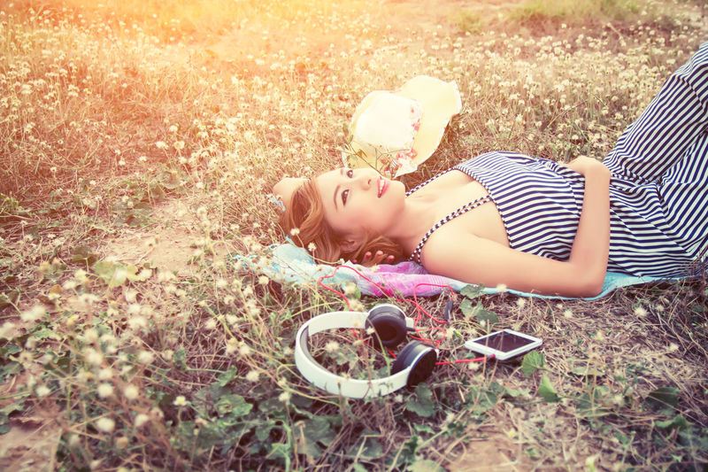 Woman With Personal Accessory Lying Down On Field