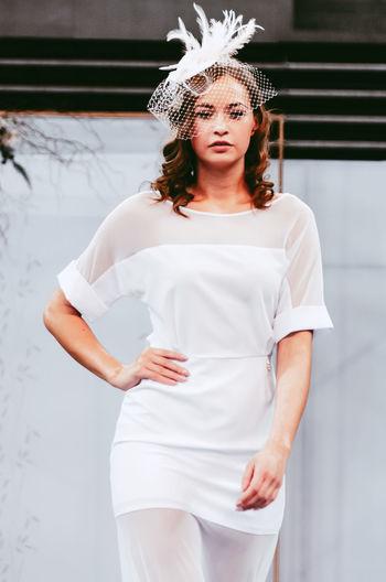 Female fashion model standing against wall