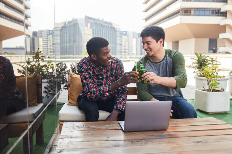Smiling friends holding beer sitting outdoors against building