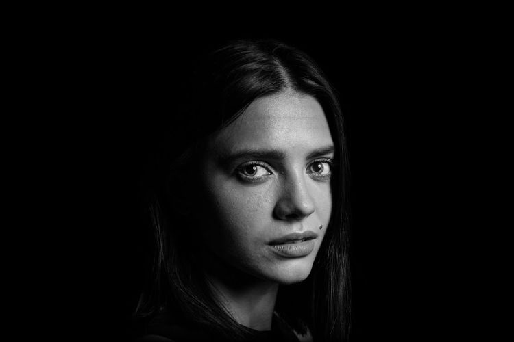 Close-up portrait of young woman over black background