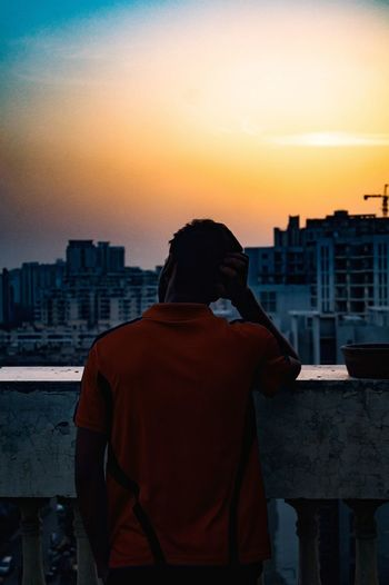 Rear view of silhouette man against cityscape during sunset